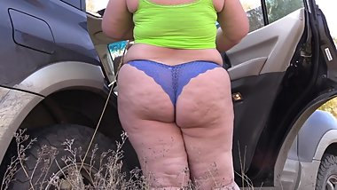fat woman changing panties near a car in a public place