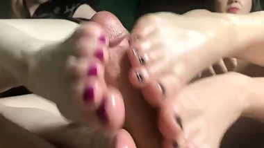 Two mature women giving footjob